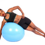 Fit woman lying on swiss ball side plank