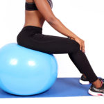 Fit woman sitting on swiss ball to workout