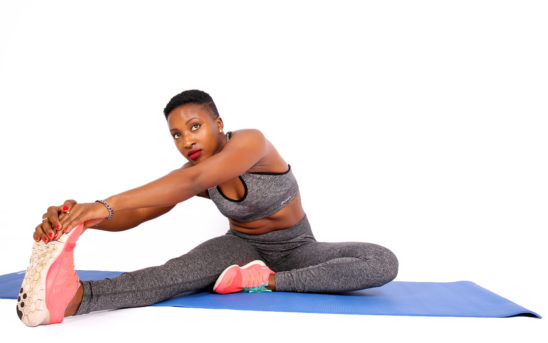 Fit woman stretching legs touching toes