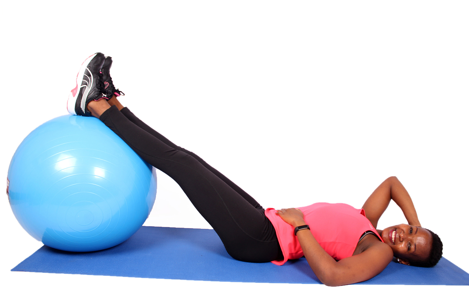 Fit woman with swiss ball smiling on yoga mat