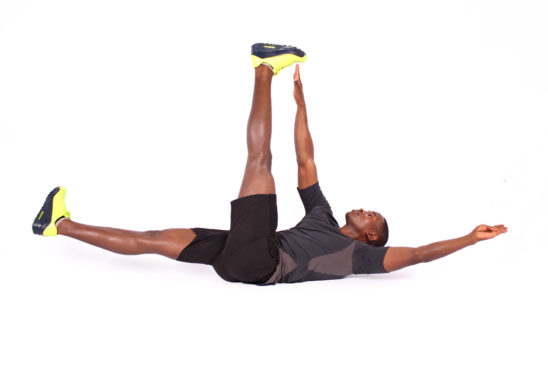 Fitness man demonstrating how to perform dead bug exercise