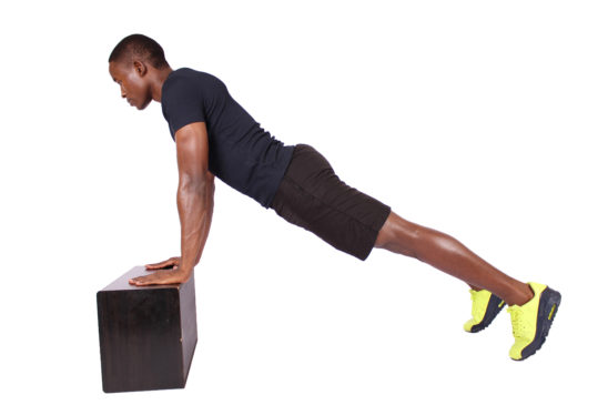 Fitness man doing incline push ups on black box