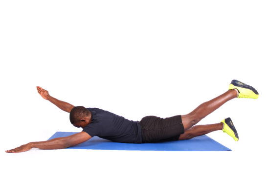 Fitness man doing swimmers lower back and core exercise