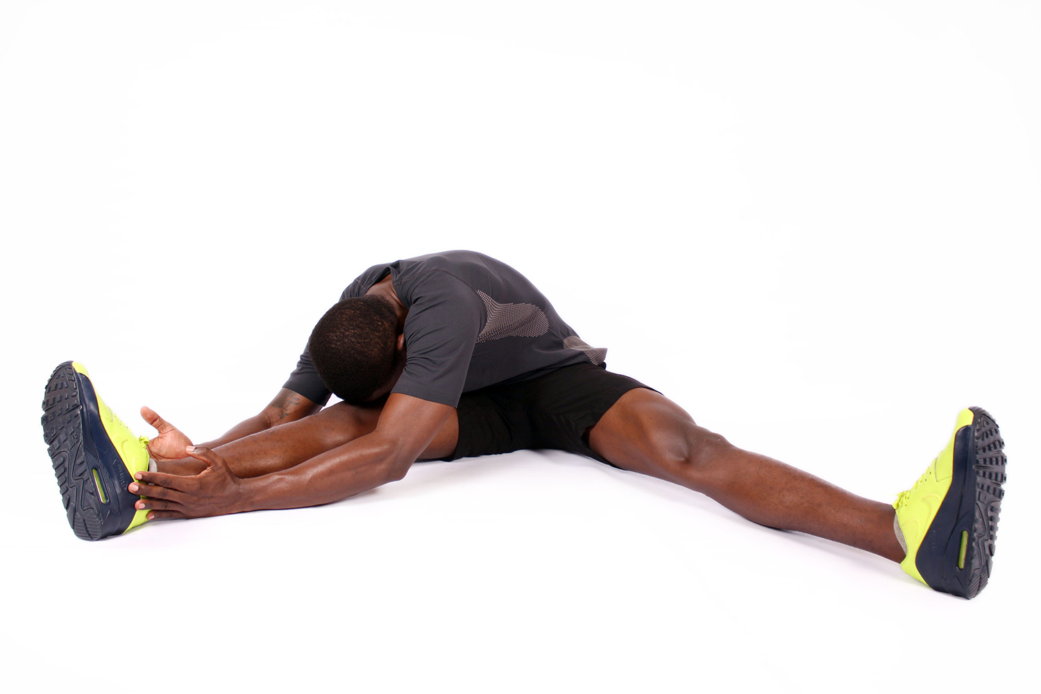 Fitness man stretching legs head to knee sitting