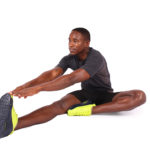 Fitness man stretching legs sitting down