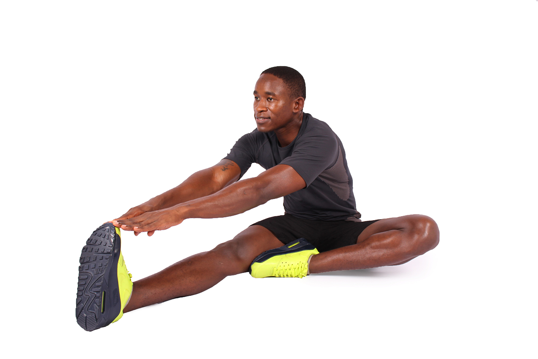 Fitness man stretching legs sitting down