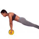 Fitness woman doing ab wheel roller exercise