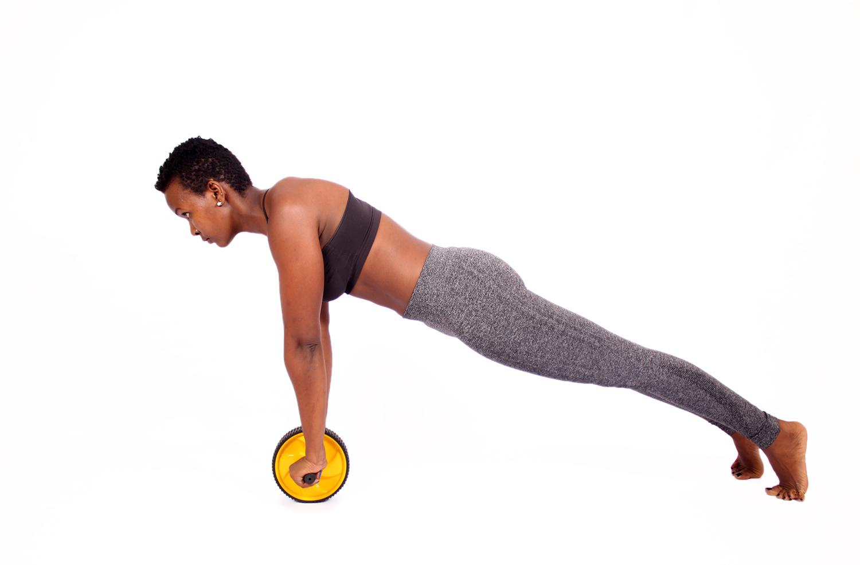 Fitness woman doing ab wheel roller exercise