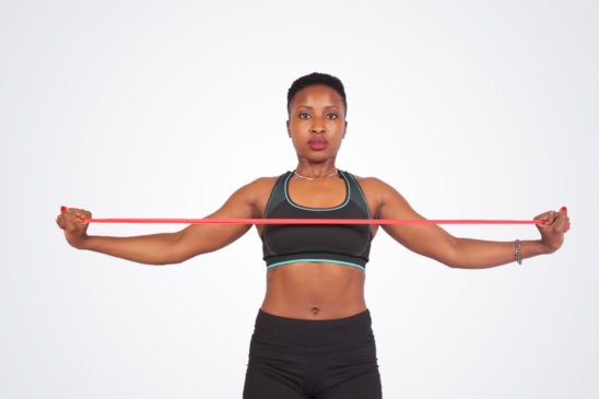 Fitness woman doing arm exercise with resistance bands