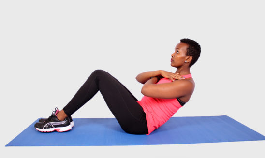 Fitness woman doing crunches and sit ups on yoga mat