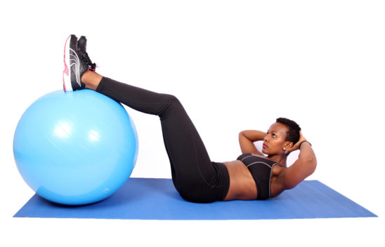 Fitness woman doing crunches with legs placed on swiss ball