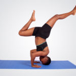 Fitness woman doing head stand legs spread apart