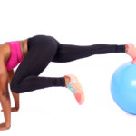 Fitness woman doing mountain climbers on swiss ball