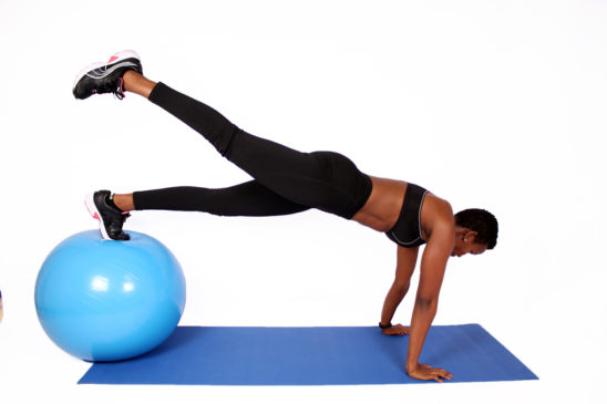 Fitness woman doing plank on swiss ball