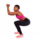 Fitness woman doing squats in white background