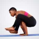 Fitness woman doing yoga pose on blue mat