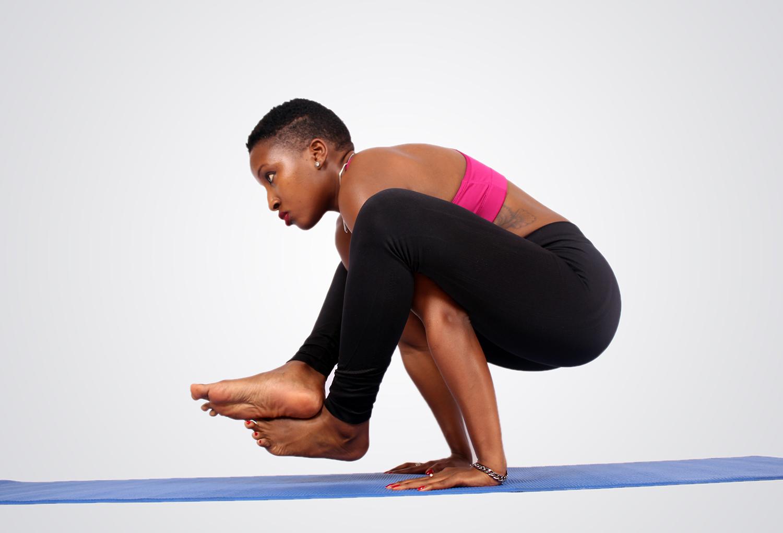 Fitness woman doing yoga pose on blue mat