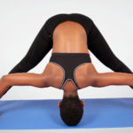 Fitness woman doing yoga stretch on yoga mat