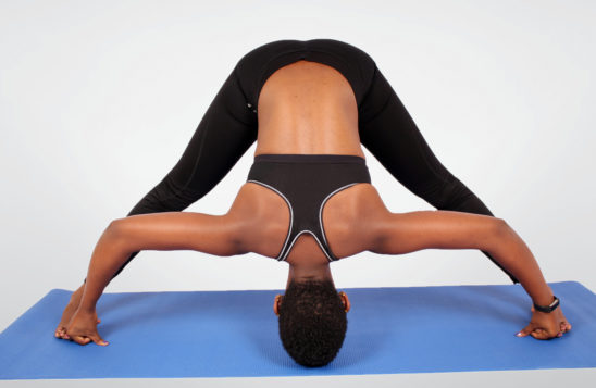 Fitness woman doing yoga stretch on yoga mat
