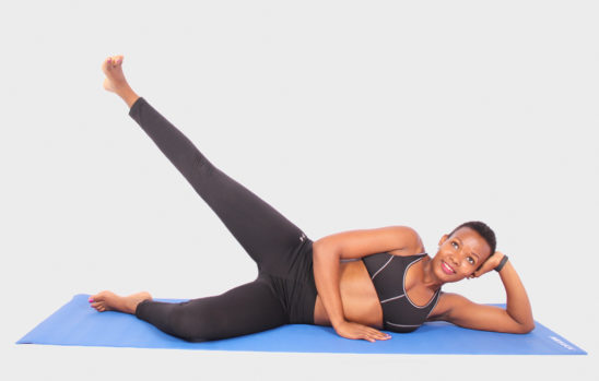Fitness woman doing yoga with leg raised