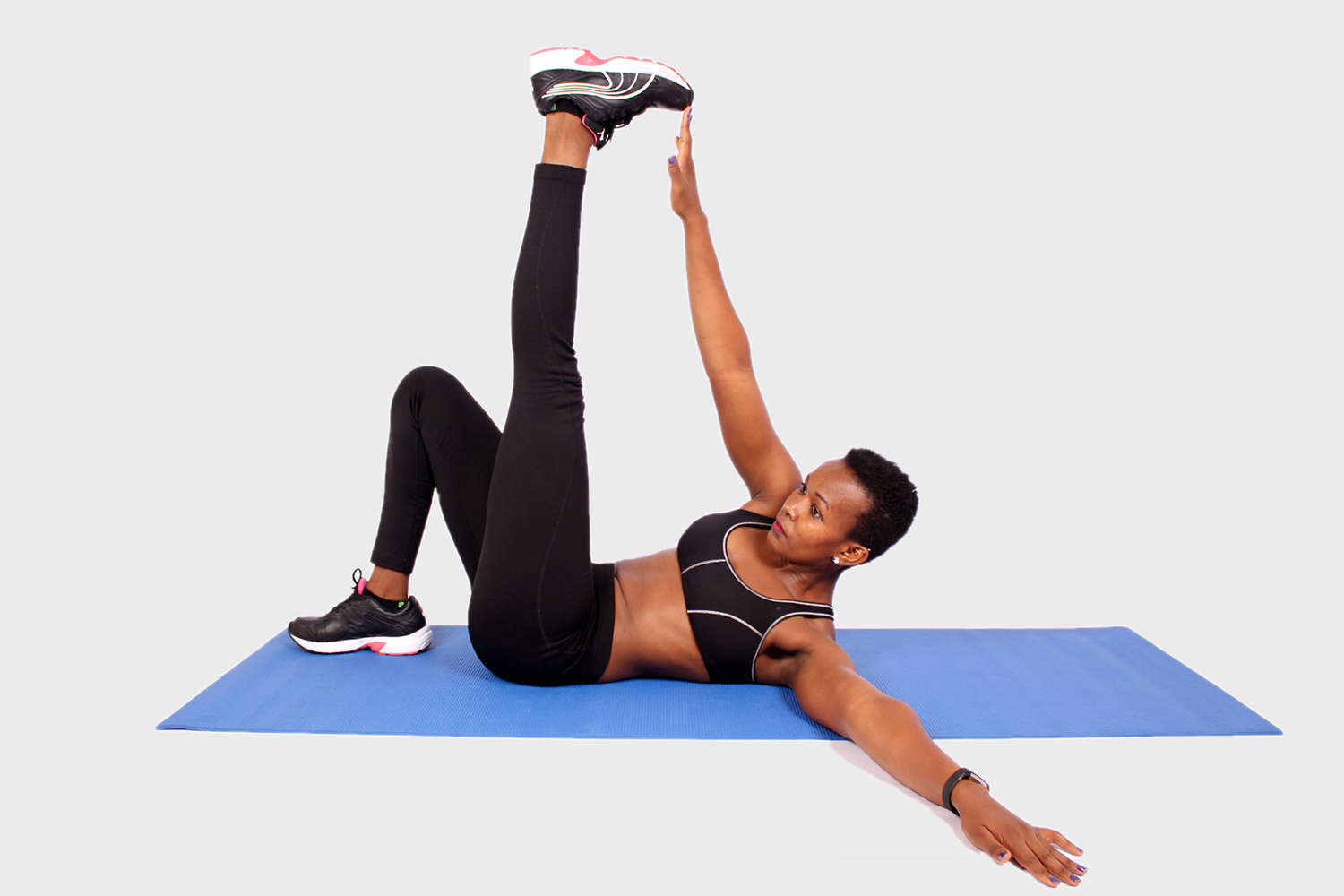 Fitness woman exercising on yoga mat with one arm and leg raised