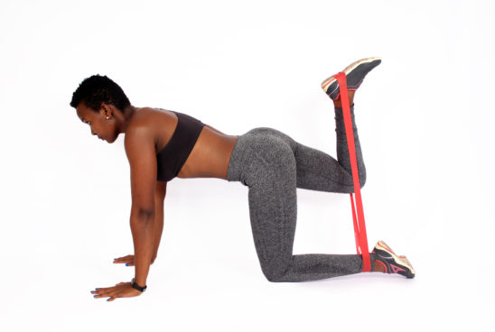 Fitness woman exercising with resistance bands donkey kicks