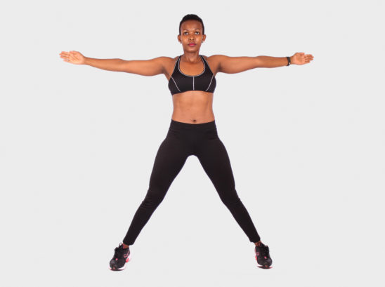 Fitness woman standing with legs and arms spread apart