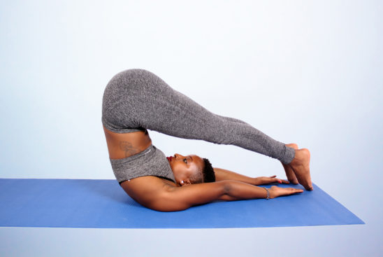 Fitness woman with tattoo doing yoga pose