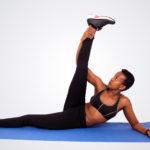 Fitness yoga woman stretching leg lying on yoga mat