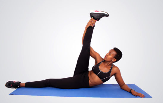 Fitness yoga woman stretching leg lying on yoga mat