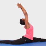 Flexible woman doing split yoga exercise