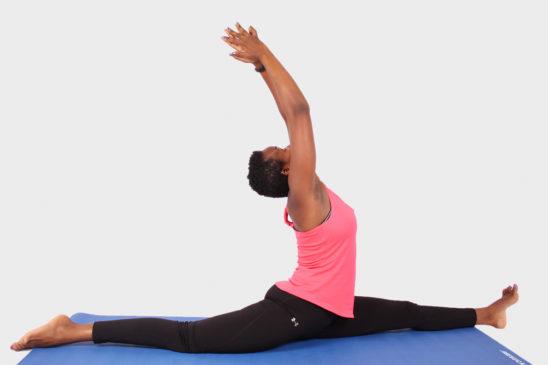 Flexible woman doing split yoga exercise