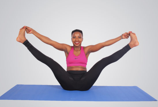 Flexible woman doing yoga pose smiling