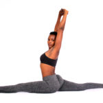 Flexible woman doing yoga split exercise