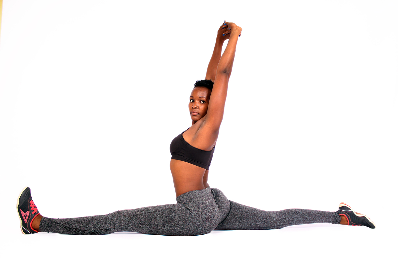 Flexible woman doing yoga split exercise