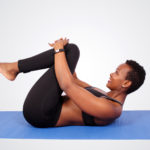 Flexible woman doing yoga stretch at lying on yoga mat