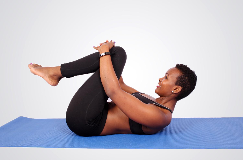 Flexible woman doing yoga stretch at lying on yoga mat