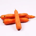 Four raw carrots on isolated white background