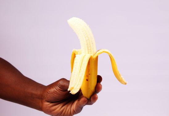 Hand holding peeled banana