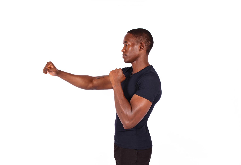Muscular athlete throwing punch boxing