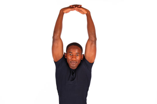 Muscular male doing shoulder stretch