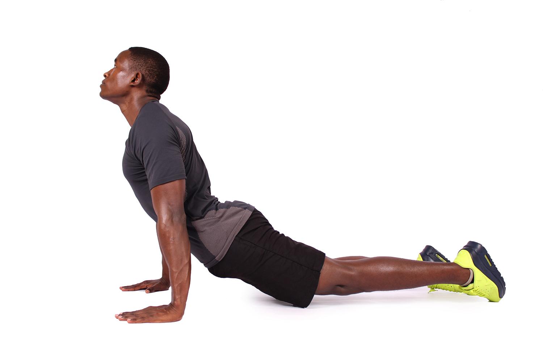 Muscular man doing divebomber push ups and yoga pose