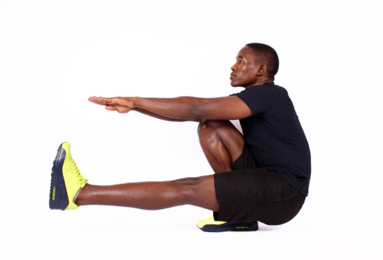 Muscular man doing pistol squat one legged squat exercise