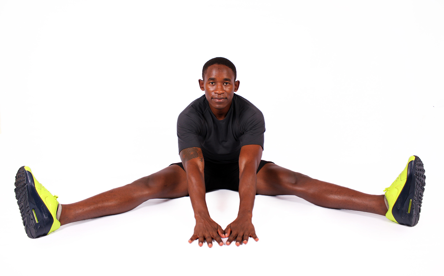 Muscular man stretching legs on white background