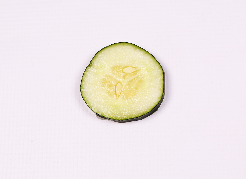 One slice of cucumber on white background
