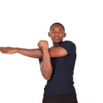 Smiling black man doing shoulder stretch