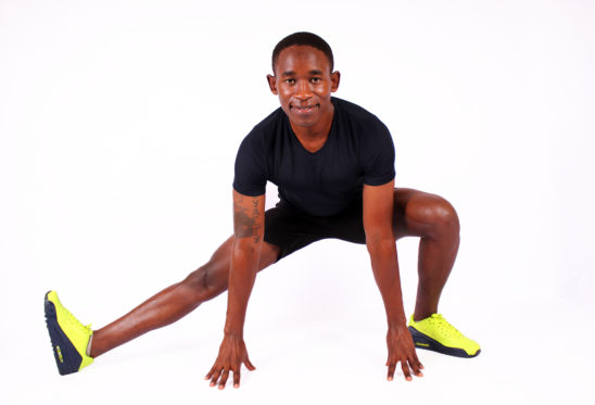 Smiling man stretching legs and hamstrings