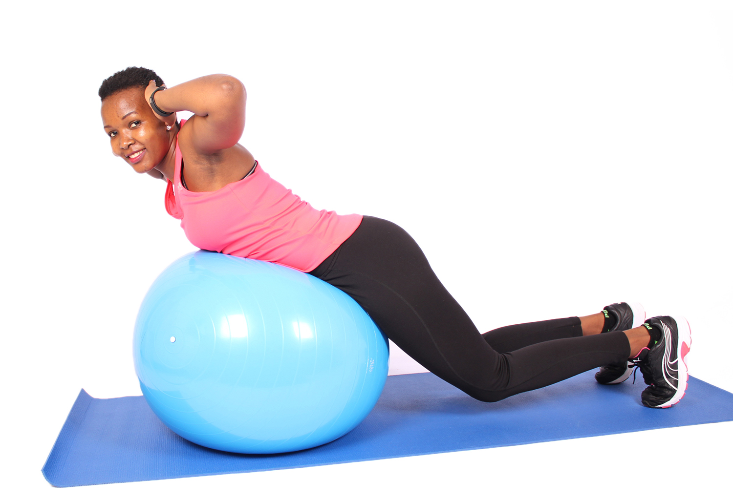 Smiling woman doing core exercise on swiss ball