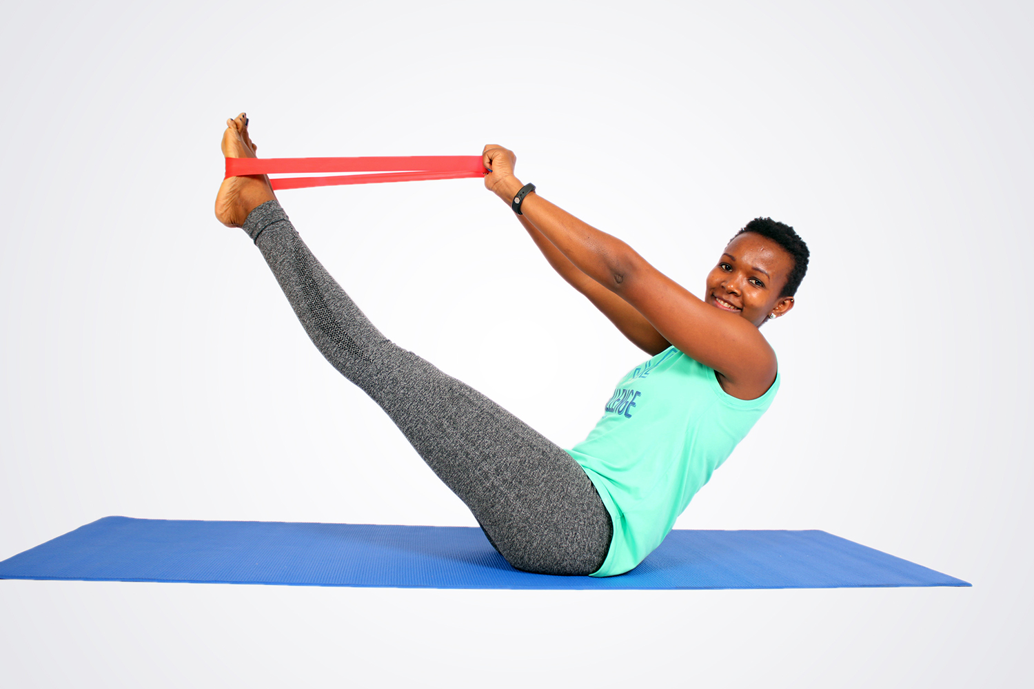 Smiling woman doing resistance band exercise on yoga mat