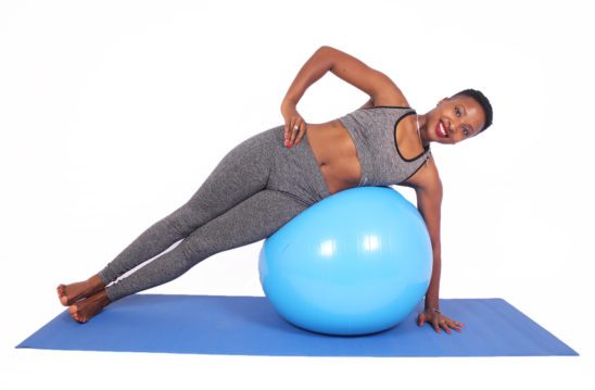 Smiling woman doing side plank with swiss ball